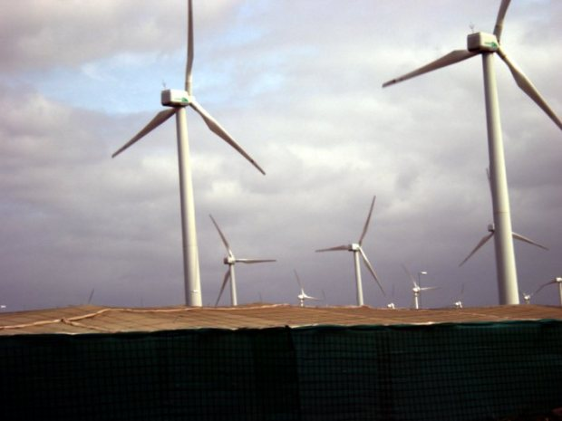 Wind turbines in Gran Canaria. Under their base, agricultural greenhouses