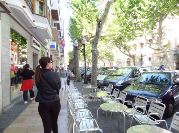 A sidewalk cafe in the morning of a working day, with cars in the street